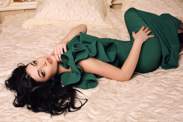 gorgeous sexy girl with dark hair in elegant green dress