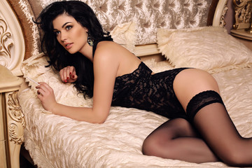 gorgeous sexy girl with dark hair in lingerie and pantyhose posing in bedroom