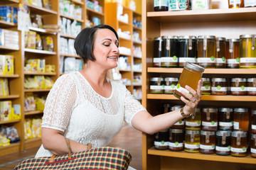 Woman choosing honey from assortment in drugstore
