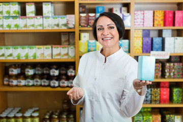 Woman in white coat promoting food additive goods in carton in drugstore