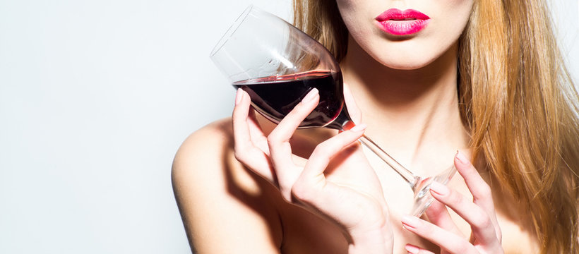 Red wine glass in female hands