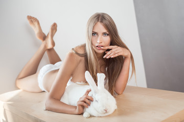 Girl playing with his pet big rabbit