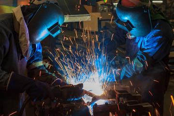 Team welder are welding in car factory