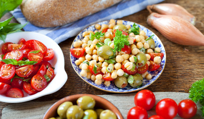 Vegetarian Mediterranean salad board - cherry tomatoes, green olives, chickpea, basil