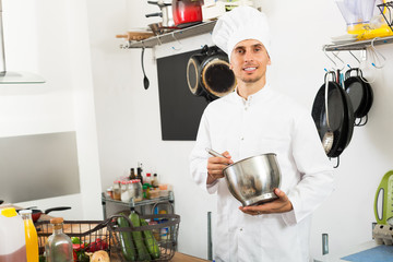 Positive young man chef cooking food at kitchen