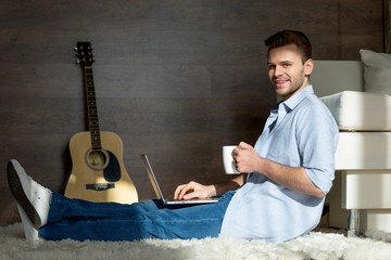 Side view of handsome young man with laptop and tea cup smiling at camera