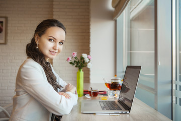 Pretty woman sitting at laptop and smiling in frame
