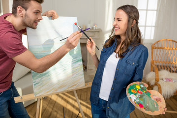Happy young couple with paintbrushes having fun while painting together