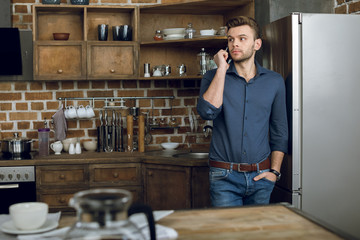 Handsome young man leaning on refrigerator while talking on smartphone
