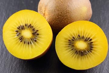 fresh yellow kiwi fruits on a slate plate