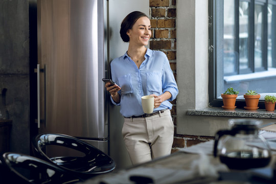 Smiling young businesswoman holding smartphone and coffee cup