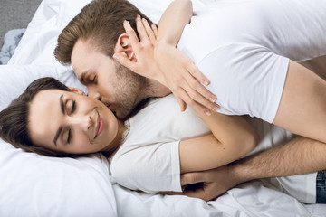 portrait of man kissing smiling woman in bed