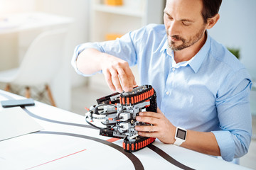 Professional adult engineer working on the robot