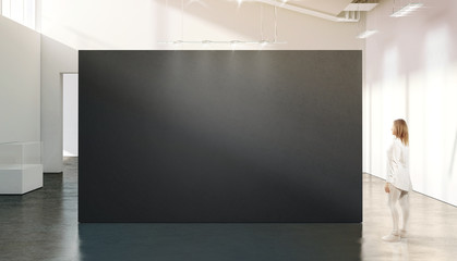 Woman walking near blank black wall mockup modern white gallery