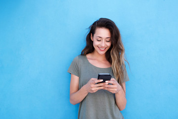 young smiling woman using mobile phone against blue background Fototapete