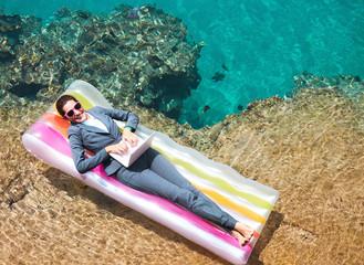 Happy businesswoman using laptop on lilo at resort