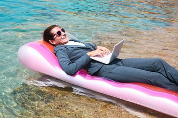 Happy businesswoman using laptop on pool raft
