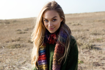 Beautiful young woman posing in a cold winter on the beach.