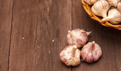 heads of garlic in a wicker basket on a wooden background
