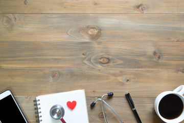 Top view of blank notepad on wooden desk with smartphone, pen, stethoscopes and coffee cup.