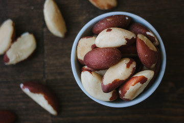 Brazil nuts on white ceramic bowl over the wooden table