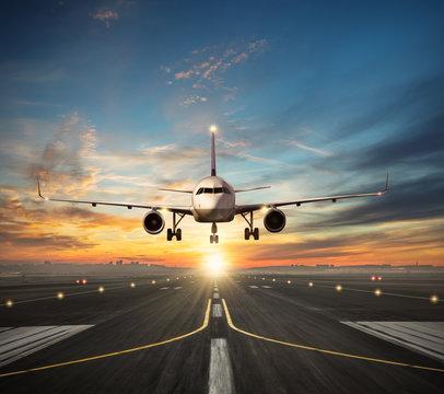 Airplane landing to airport runway in sunset light