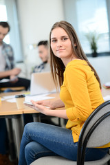 portrait of young woman in casual wear working in a creative business startup company office with coworker people in background