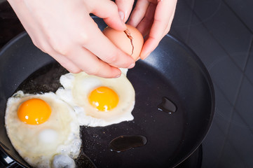Woman's hands breaking breaking eggs into frying for Sunday's breakfast. Healthy eating concept