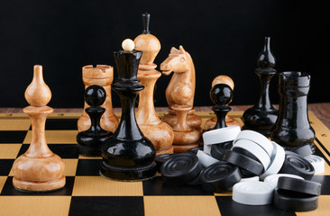 The chess pieces and pile of checkers placed on the chessboard.