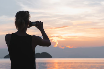 Man taking photo in picturesque sea scenery at sunset
