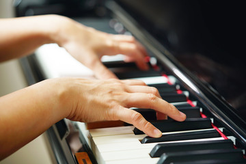 Scene of pianist hands from beside angle playing piano. Selective focused..