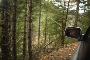 Mans reflection in wing mirror of vehicle, driving by woodland