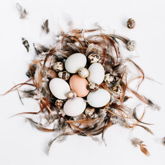 White, brown Easter eggs, quail eggs in nest decorated with feathers on white background. Flat lay, top view. Traditional spring concept.