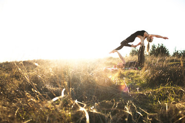 Two women in acro yoga position in field