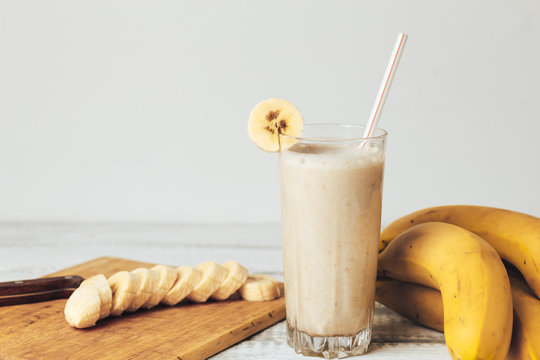 Fresh homemade banana smoothie, cutting board and bananas on white rustic wood