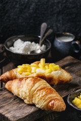 Breakfast with two croissant, butter, cottage cheese, coffee and sliced mango fruit, served on wood chopping board over old wooden background. Close up.