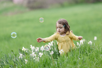 Child playing with bubble in the field.