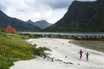 Children running on a beach in the northern part of Lofoten Islands, Norway.