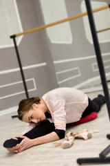 pretty young graceful ballet dancer warms up in ballet class sitting in the twine