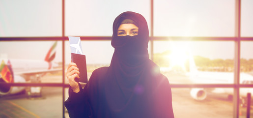 muslim woman with ticket and passport at airport