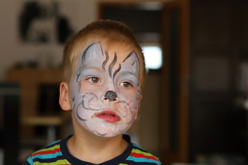 Boy with blue butterfly painted on his face