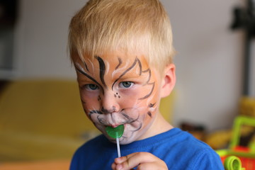 Boy with orange lion painted on his face licking lollipop
