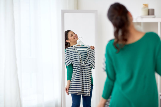 happy woman with shirt looking to mirror at home