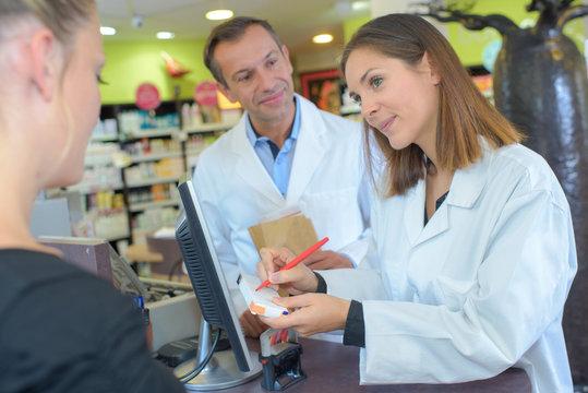 Pharmacist explaining medication to customer