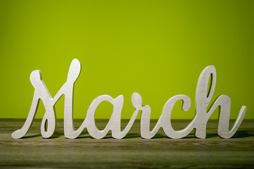 Close Up March word carved out of wood on green background. Spring beginning concept