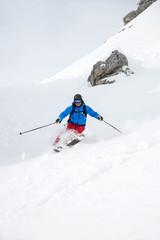 Skifahrer im Tiefschnee mit Felsen