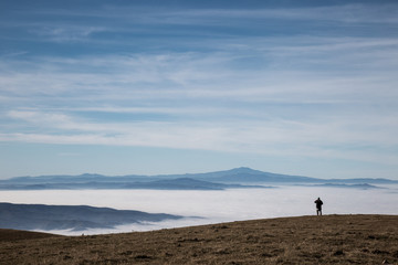 A man in a mountains scenery, with fog and big blue sky