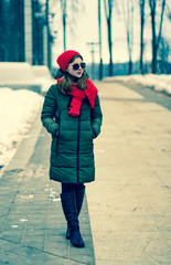 Portrait of a beautiful young girl in sunglasses and red hat with a scarf, which is on the park alley