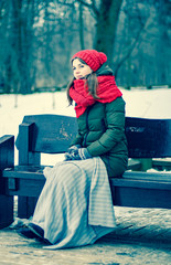 Portrait of a beautiful young girl in a red cap with a scarf, which sits under a blanket on a bench in the park in winter