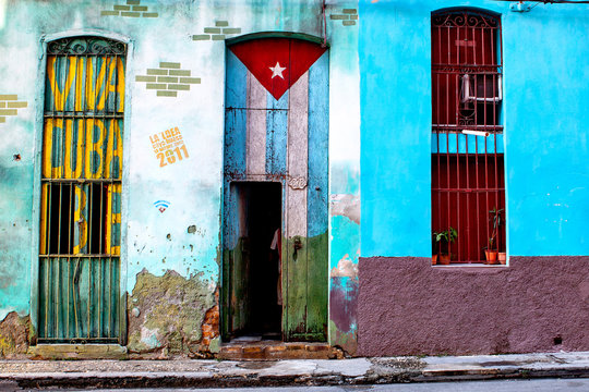 """Old shabby house in Central Havana painted with the Cuban flag and a """"Viva Cuba"""" Libre writing"""